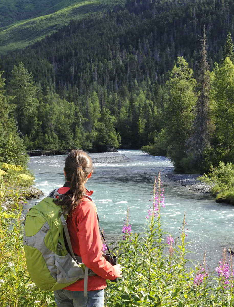 Woman hiking along river in a mountain range